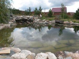 Искусственный пруд с мощением верхней ступени камнем